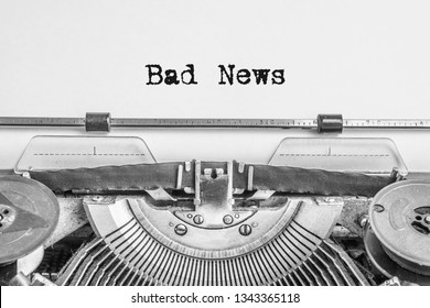 Bad News typing text vintage typewriter with black ink heading on aged paper