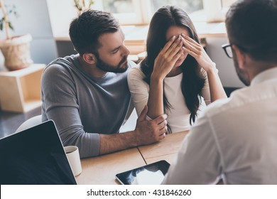 Bad news. Young man comforting his wife while sitting together with psychologist