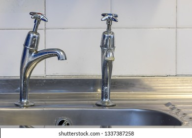 Bad plumbing. Badly fitted sink tap. Faucet with limescale. Old chrome kitchen or bathroom taps in close up.