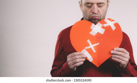 Bad relationships, breaking up, sadness emotions concept. Sad adult man holding broken heart fixed with plaster bandage, on grey