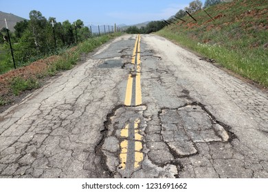 Bad road surface - damaged transportation infrastructure in California, USA.