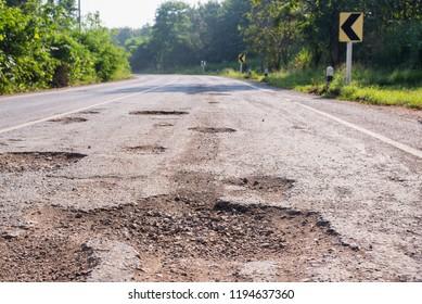 Bad roads. Hole in the asphalt, the risk of movement by car, bad asphalt, dangerous road, potholes in asphalt, pit unsafe hole road concept. Way markings in the pit.