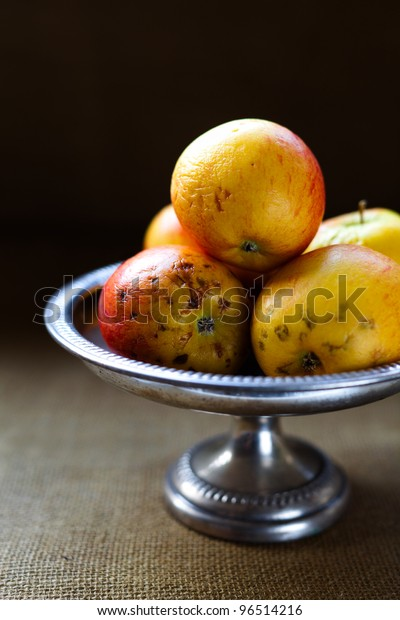 Bad rotten apples on a silver pedestal dish against black