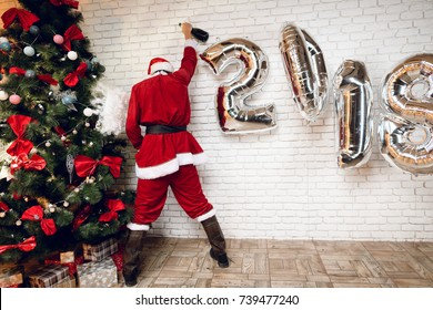 Bad Santa Claus urinate under the New Year tree after a tumultuous party. He hardly stands on his feet. next to a beautiful Christmas tree.