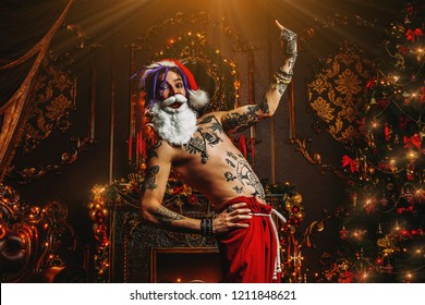 Bad Santa concept. Portrait of a nude tattooed Santa with purple dreads demonstrating antisocial behavior, rudeness and aggression.