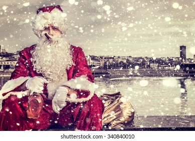 Bad Santa holding bottle of brandy and cigar in his mouth