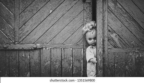 A bad and scary doll looks out of the door and scares people. Halloween and horror. Waiting for the victim. Bad sleep. Black and white photography.