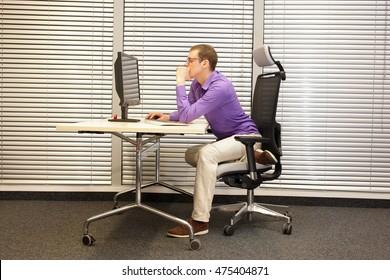 bad sitting posture at workstation - man at office work