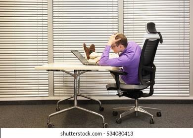 bad sitting posture at workstation - man with legs on desk