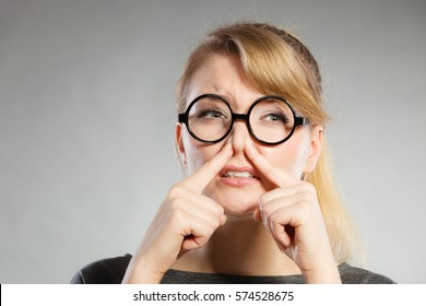 Bad smell concept. Young woman feels disgust pinches her nose with fingers because of odor stench unpleasant stink. Facial reaction.