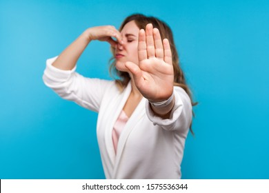 Bad smell. Portrait of woman with wavy hair in white jacket pinching her nose and showing stop gesture, expressing disgust to unpleasant odor, fart gases, her eyes closed with abhor. blue background
