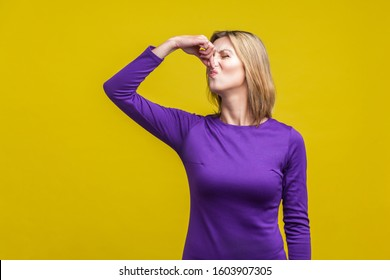 Bad smell. Portrait of young woman in purple dress standing pinching her nose with fingers to hold breath, disgusted by stinky intolerable smell. indoor studio shot isolated on yellow background