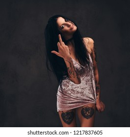 Bad tattooed girl wearing a nightie shows middle finger, fuck you with a sign.