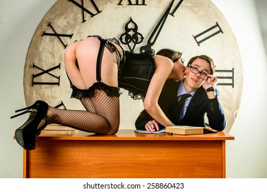 Bad Teacher. sexy teacher is seducing to her student who is redding. sexy girl is seducing a man who is reading on a desk. A sexy female teacher and her student in front of the big clock