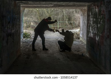 Bad thief with a knife attack another person in a dark tunnel and demands his money. Concept: crime and security