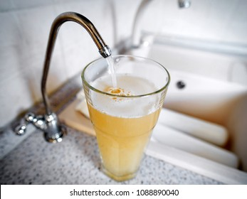 bad water is poured from the tap into the glass. Dirty water can be a source of disease