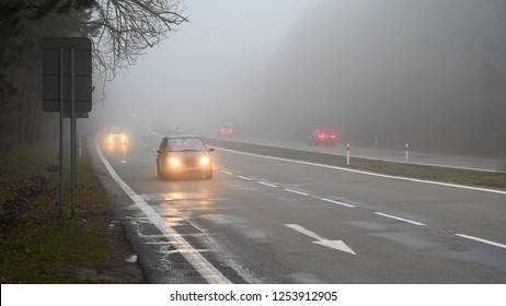 Bad weather driving - foggy hazy country road. Motorway - road traffic. Winter time.