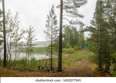 Bad weather for a recreation. Damp and rainy over the lake. On the shore among the bushes and trees there is a car and a tent, people hid from the damp.