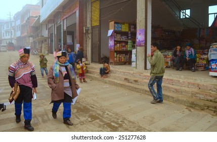 BADA, CHINA, NOVEMBER 18, 2013: People are walking through main street of chinese mountain village bada which is situated among yuanyang rice terraces in yunnan province.