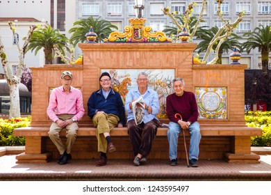 Badajoz, Spain - Circa April 2017: Four elderly friends sitting on a decorated bench at the Paseo de San Francisco square in Badajoz