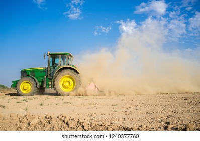 Badajoz, Spain - Oct 11th 2017: Farm tractor preparing dusty soil affected by drought. Drought and agriculture concept