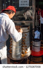 Badaling, China - July 3 2016: A chef a a Chinese restaurant is looking after the Dim sum dishes in front of his eatery