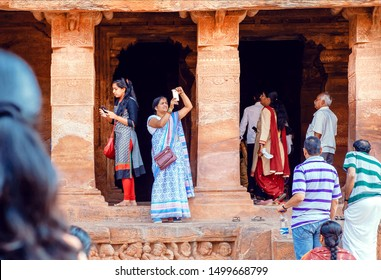 BADAMI, INDIA - FEB 10: Older woman making picture by iphone in crowd of tourists near the 6th century Hindu temple with caves on February 10, 2017. Population of Karnataka state is 62,000,000 people
