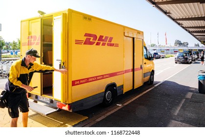 BADEN, GERMANY - MAY 11, 2018: Male courier closing door of DHL yellow delivery van after delivering the on time delivering package parcel