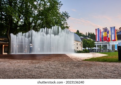 """Baden-Baden, Germany - Aug 10 2021: People at the water pavilion by Danish artist Jeppe Hein at sunset in front of the Kurhaus in Baden-Baden, Germany. Exhibition """"Kunst findet Stadt""""."""