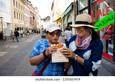 BADEN-WURTTEMBERG, GERMANY - AUGUST 25 : Asian women mother and daughter travel and eating pizza on street of Heidelberg old town on August 25, 2017 in Baden-Wurttemberg, Germany