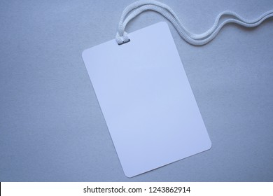 Badge blank plastic empty security. Name id card badge with cord on grey background, empty space for text.