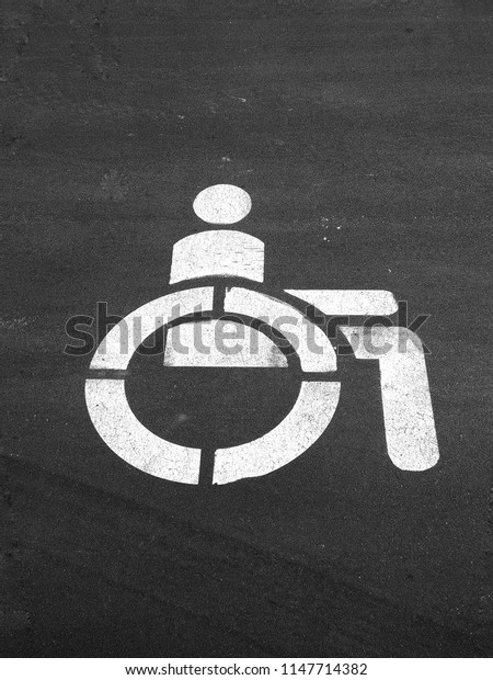 Badge of disability on the asphalt. Road marking, sign of a person with disabilities