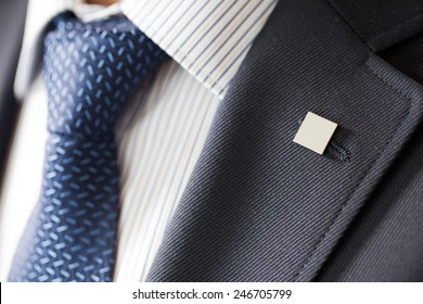 badge on the lapel of his jacket men's shirt with a blue tie