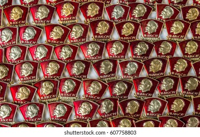 Badges of members of the Komsomol - the silhouette of Lenin on the background of the red banner. Background from the Komsomol emblems of the USSR.