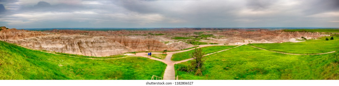 Badlands National Park, South Dakota, June 6, 2018: A couple walks to an overlook in Badlands National Park which is full of awe inspiring landscapes and stark geologic formations.