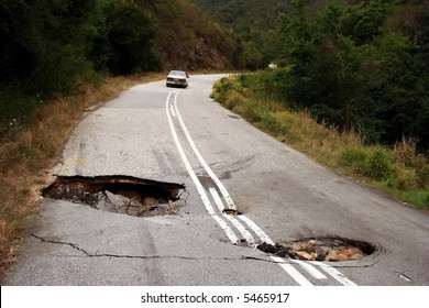 A badly damaged road with sink holes due to heavy rain falls