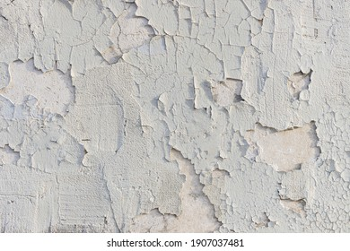 Badly fixed white building facade wall covered with cracks in stucco and painting. Very flaky texture. Exposed substrate. Missing patches of paint. - Shutterstock ID 1907037481