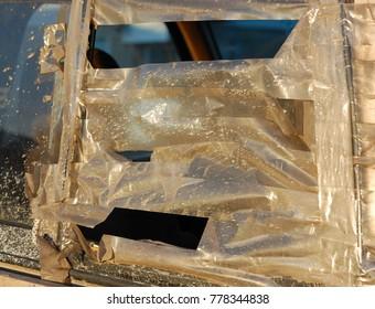 badly taped over damaged truck window in sunlight dirt splattered