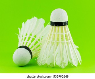 badminton ball in front of green background
