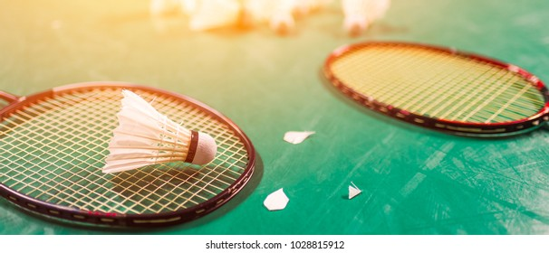 Badminton ball (shuttlecock) and racket on court floor banner panoramic crop for copy space.