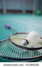 Badminton ball (shuttlecock) and racket on court floor.