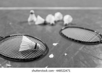 Badminton ball (shuttlecock) and racket on court floor. Black and white