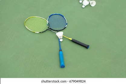 Badminton balls and paddles on a court outdoors