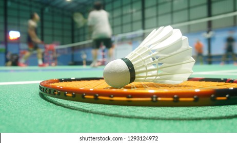 Badminton balls placed on badminton rackets in the field