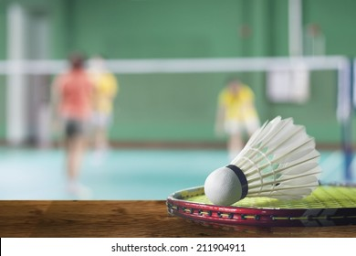 Badminton courts with players competing.