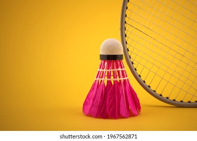 Badminton feather shuttlecock near badminton racket over a yellow background with copy space