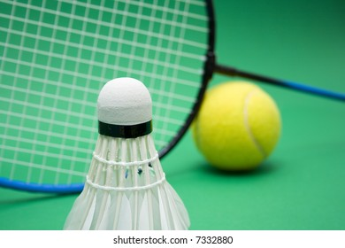 Badminton game equipment with tennis ball on the green background