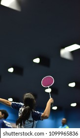 A badminton girl player is aiming and ready for a big smash at the coming shuttlecock hitting back from the opposite side while her partner is waiting upfront in a practice game in the indoor court.