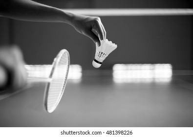Badminton player holding a racket ready to serve in a court in black and white
