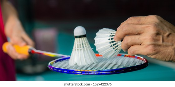 Badminton player holding racket with used Badminton shuttlecock on top and hand of service judge hold new shuttlecock to change the new one with blur background, most popular sport in Southeast Asia